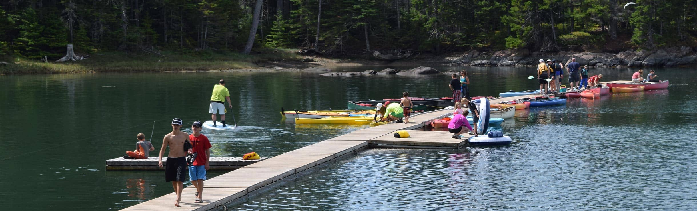 campers on dock with kayaks, inter-tubes and paddleboards